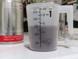 A measuring cup with coffee grounds in it, measuring up to about two thirds of a cup.