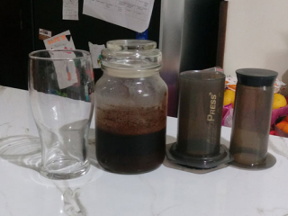 A pint glass, a jar with overnight cold brew coffee, and an AeroPress coffee maker sitting on a bench.