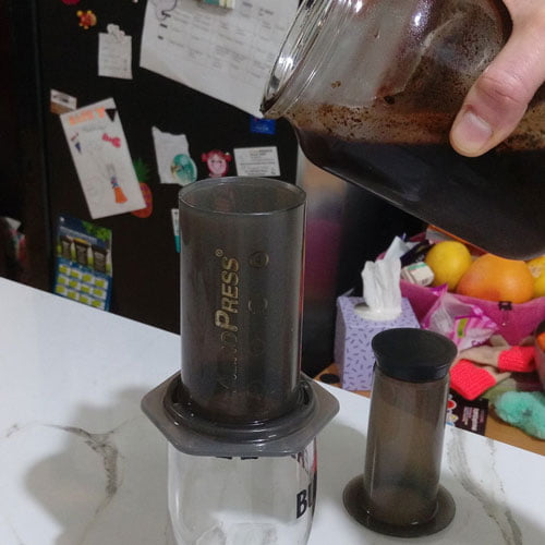 A jar with overnight cold brew being poured into an AeroPress on top of a pint glass.