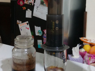 Pressing the AeroPress with cold brew coffee inside into a pint glass with ice.