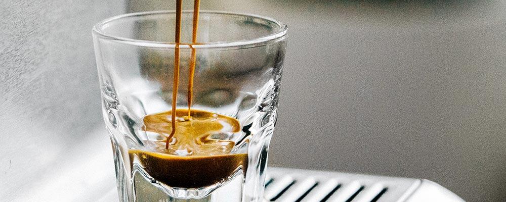 Espresso coffee pouring into an espresso glass from an espresso machine