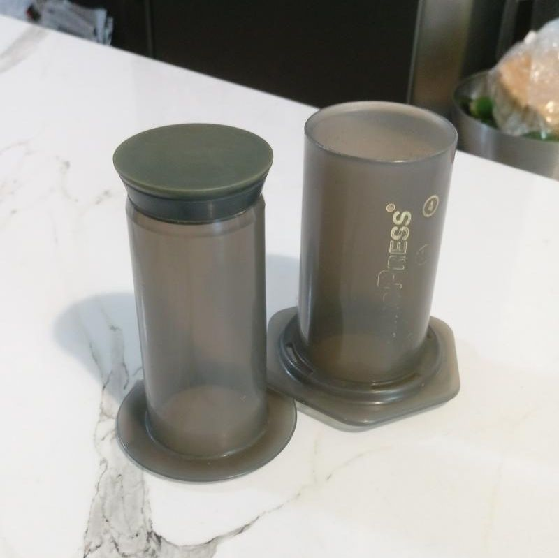 An AeroPress chamber and plunger sitting on a kitchen bench.