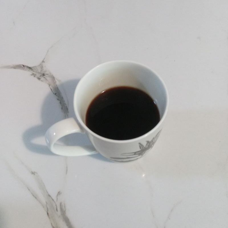 A coffee mug with coffee inside that has just been freshly pressed by an AeroPress.
