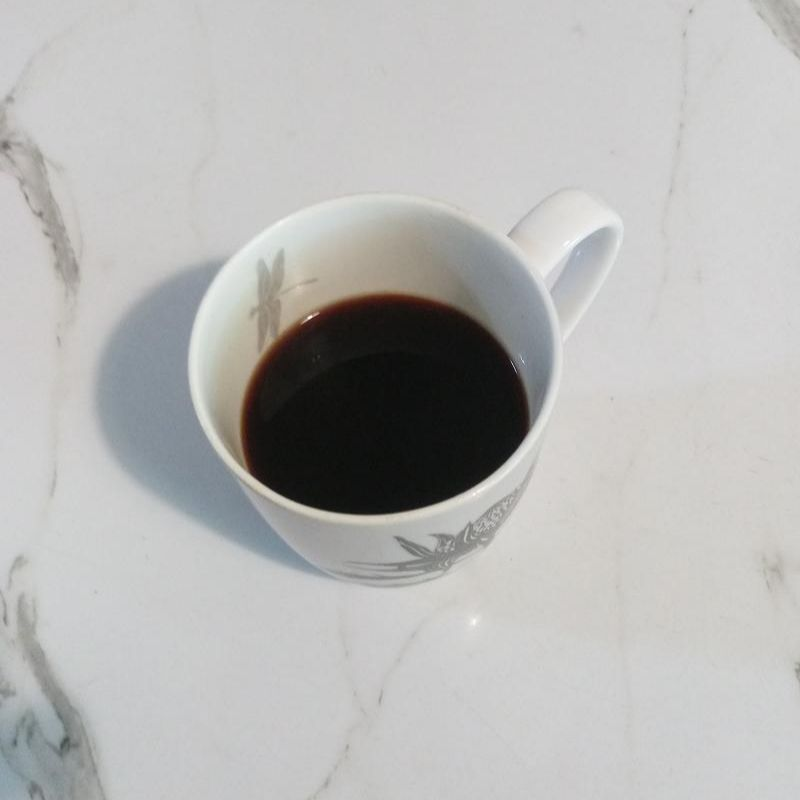 A cup of coffee that has just been brewed with an AeroPress.