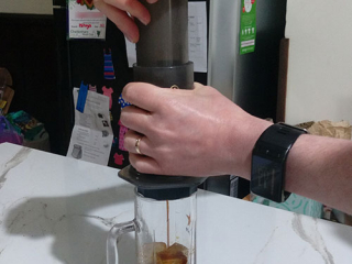 Pressing cold brew from AeroPress with Fellow Prismo into glass mug with ice.