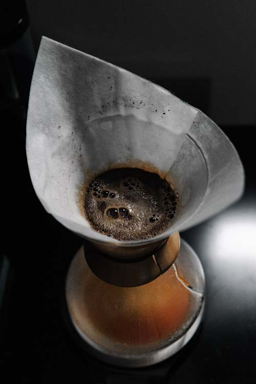 A view of the top a Chemex coffee maker with wet coffee grounds sitting in filter.