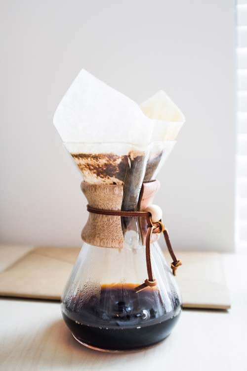 A Chemex coffee maker with coffee dripping through the paper filter.
