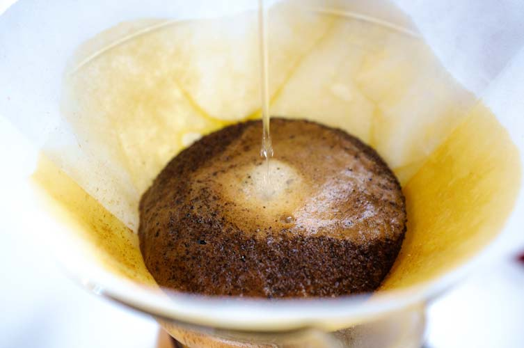 A close-up of making coffee in a Chemex coffee maker.