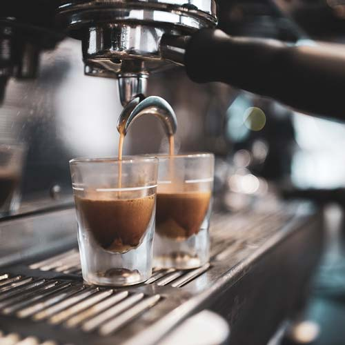 Close up of a commercial espresso machine with espresso coffee pouring into two espresso glasses.
