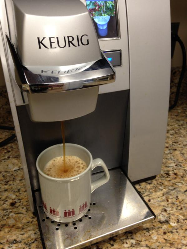 A Keurig Coffee Maker brewing a cup of coffee from a K-Cup.