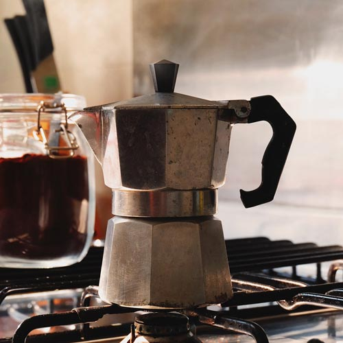 A side-view of a Moka Pot on a gas stove with some ground coffee in a glass jar in the background.