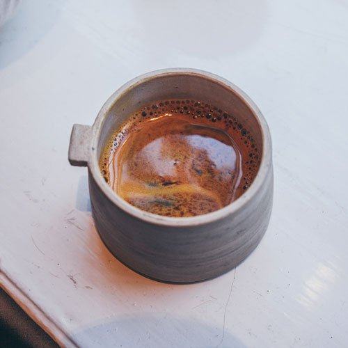 Close-up of a ceramic cup with coffee inside with crema on top.