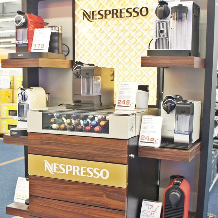 A Nespresso stand with various Nespresso coffee makers and Nespresso pods on display at a department store.