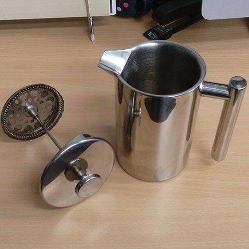 A stainless steel coffee plunger sitting on a table.
