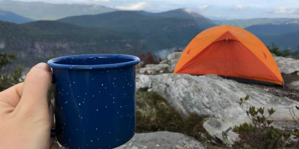 A hand holding out a camping mug with a tent and mountains behind.
