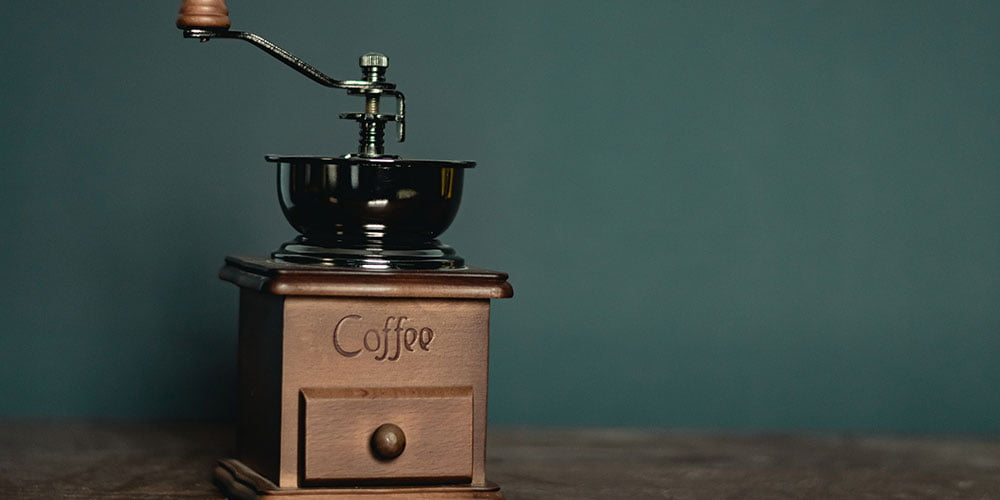 A hand coffee grinder sitting on a bench