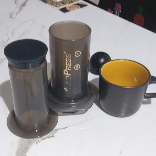 Some of the things you need to complete one fo the Fellow Prismo recipes - an AeroPress with Fellow Prismo, coffee cup and coffee scoop sitting on a kitchen bench.