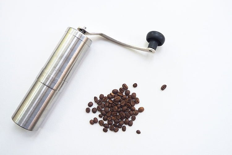 A hand coffee grinder for camping with some coffee beans