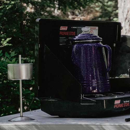 A coffee percolator that's blue with white speckles sitting on a portable camping stove.