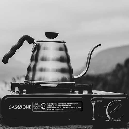 Black and white image of a gooseneck kettle on a portable gas camping stove, which is one way how to make coffee when camping.
