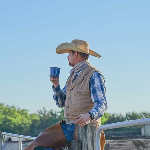 A cowboy holding a cup of coffee.