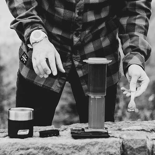 Black and white image of person showing how to make coffee when cmaping with an AeroPress coffee maker.