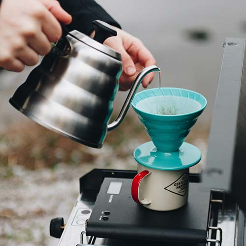 Pouring hot water from a Hario Buono kettle into a Hario V60, sitting on a coffee mug. This is another way how to make coffee when camping.