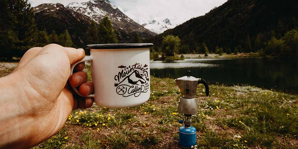 A hand holding a cup of coffee near a moka pot on a portable stove, near a lake with mountains in the background.