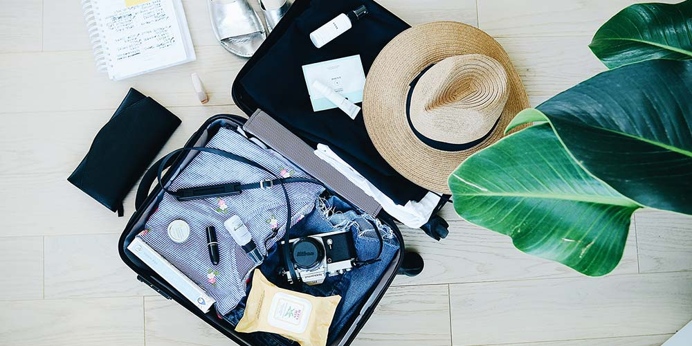 An open suitcase with various items inside and laid around it, including a hat, camera, shoes and notebook.