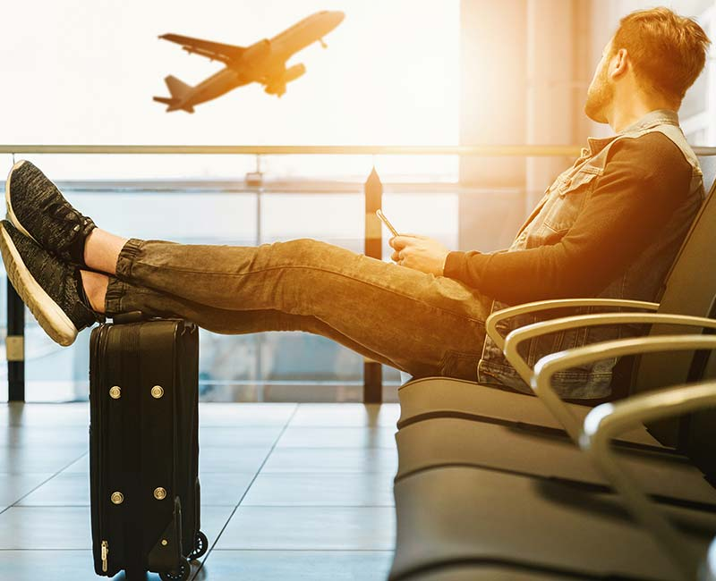 Man sitting in an airport departure area with feet up resting on his luggage, looking out the window at a departing aeroplane.