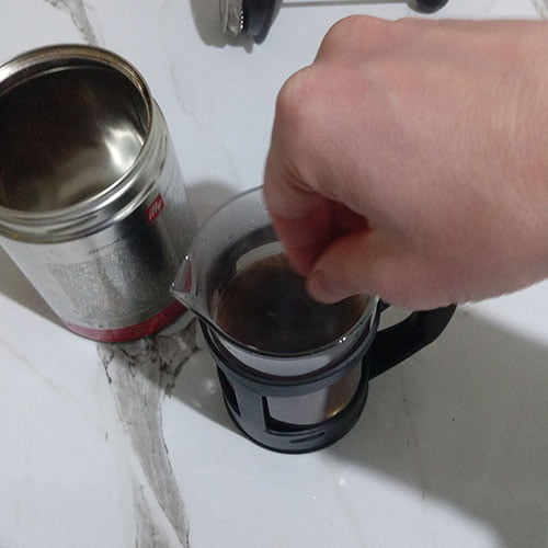 stirring the brewing coffee with a teaspoon