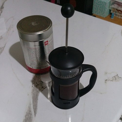 coffee plunger with hot coffee inside and lid on sitting on bench