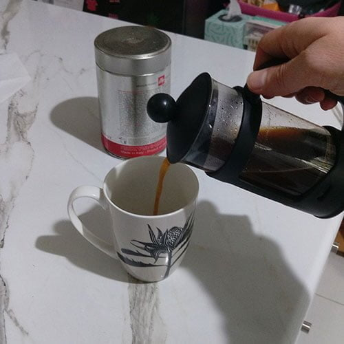 pouring hot coffee from the coffee plunger into a coffee mug