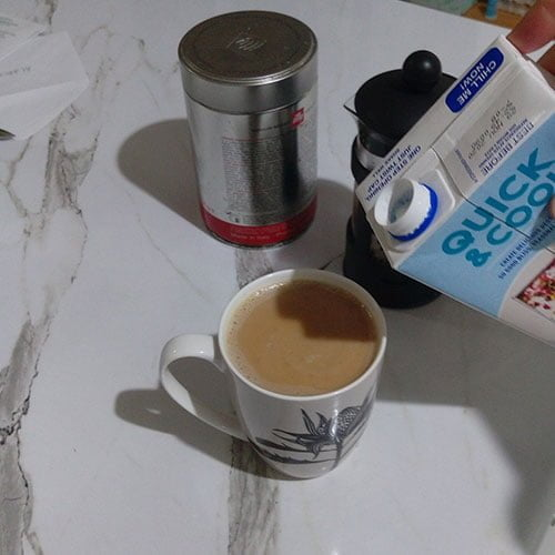 coffee cup with coffee with milk inside and milk carton