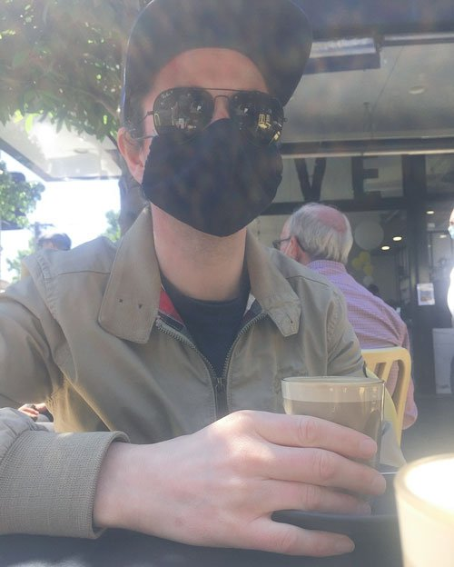 Marty wearing a mask and sunglasses at a cafe holding a cafe latte.