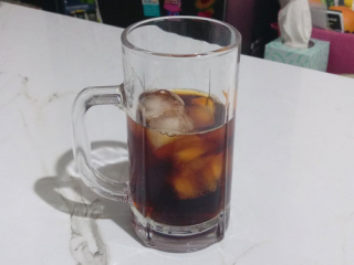 A glass with ice and some cold brew inside, made with the AeroPress and PuckPuck.