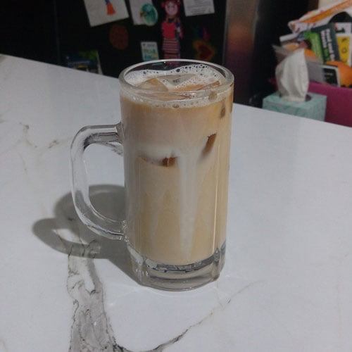 A glass of cold brew made by the PuckPuck with ice and milk.